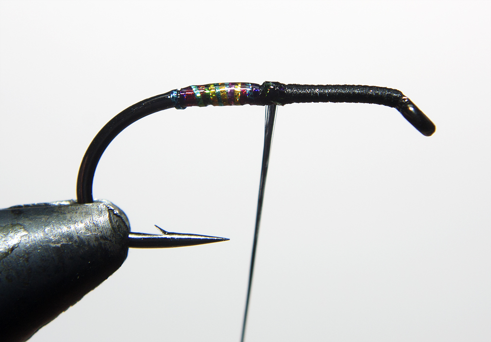2. Tie in Tinsel and wind back toward hook bend then rib it back, Apply deer Creek UV resin to secure Tag.