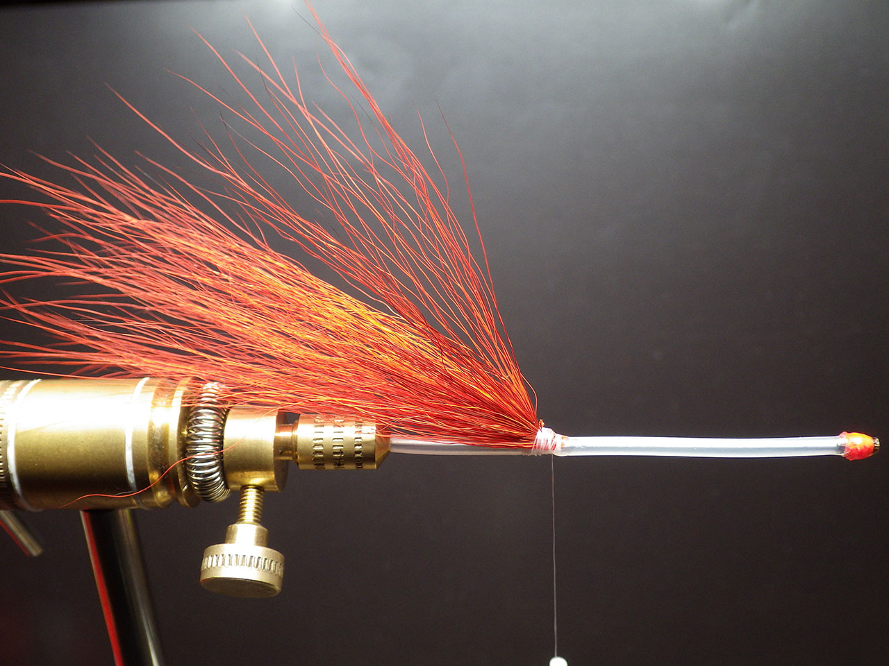 1. After fixing the tube in your vice, fix a first pinch of orange bucktail with your thread, leaving 4 to 5 cm of the sleeve free, for sliding the silicon sleeve which serves to block your dressing. Apply a generous amount of superglue.